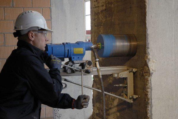 Алмазное бурение отверстий в бетоне с использованием специального электроинструмента.