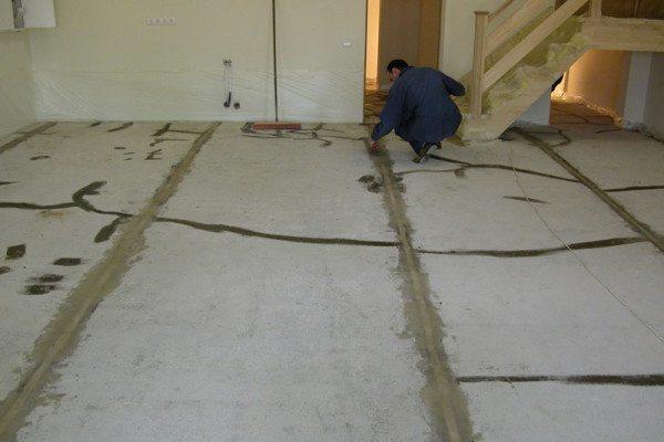 Бетонный пол с заделанными трещинами и маяками под стяжку