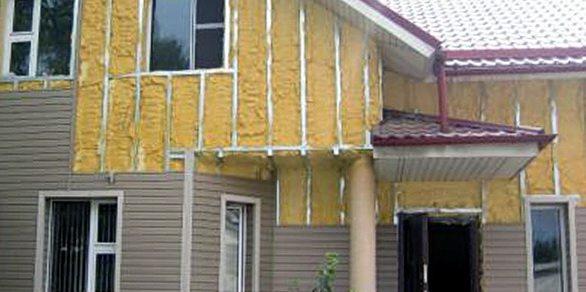 Фотография, показывающая часть дома покрытого сайдингом и не зашитые области с профилями и утеплителем