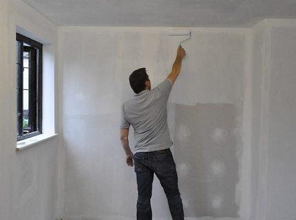 На фото - нанесение грунтовки на гипсокартонные стены
