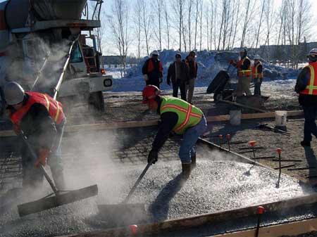 На фото - процесс укладки предварительно нагретого бетона
