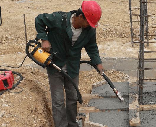 На фото – используется портативный вибратор для бетона
