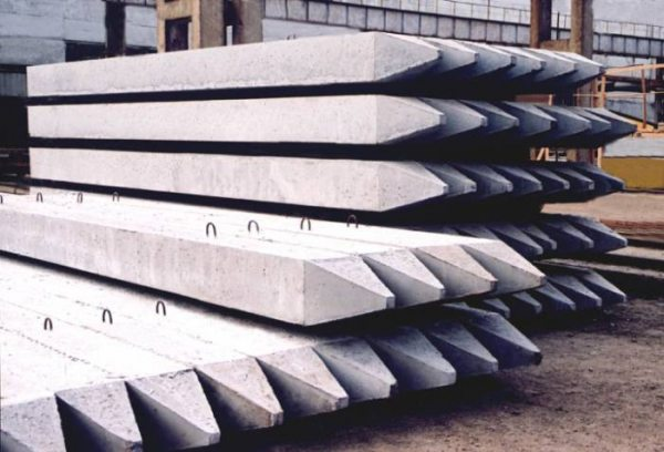 На фото: готовые бетонные изделия – сваи, которые требуют как доставки, так и установки с помощью специального оборудования