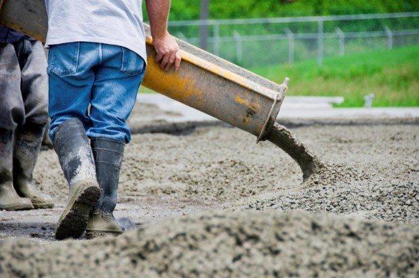 На фото показан процесс укладки бетона из автомиксера.