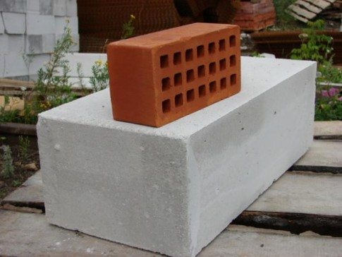 На фото видна разница между обычным кирпичом и газобетонным блоком.