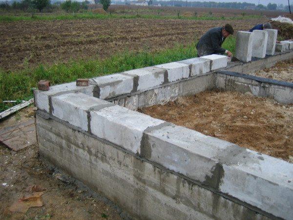 Установка первого ряда из пеноблока на бетонный ленточный фундамент
